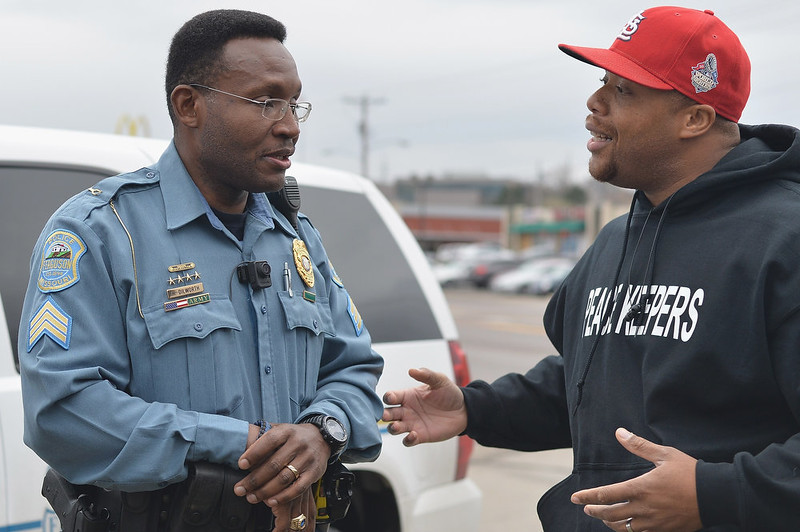 . Sergeant Harry Dilworth (L) of the Ferguson Police Department speaks with local citizen and peacekeeper, Paul Muhammed (R) in Ferguson, Missouri on November 22, 2014. Tensions rose on November 22 in the troubled St Louis suburb of Ferguson, with a grand jury poised to decide whether to prosecute a white police officer for killing an unarmed black teenager. US President Barack Obama has called for calm, Missouri\'s governor declared a state of emergency and activated the state National Guard, and the FBI has deployed an extra 100 personnel in the city.Police helicopters trained search lights over Ferguson late Friday as a small gaggle of protesters braved the cold to demand that officer Darren Wilson stand trial for shooting 18-year-old Michael Brown on August 9. Michael B. Thomas/AFP/Getty Images