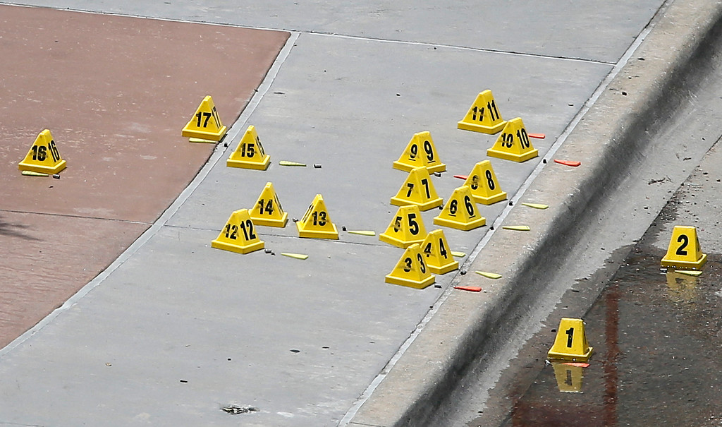 . Evidence markers sit by bullet casings on a sidewalk and street by the Dallas police headquarters where an attack on the police occurred in the earlier morning hours Saturday June 13, 2015, in Dallas. A man suspected of spraying Dallas Police Headquarters with gunfire early on Saturday has been found dead in a van after a police sniper shot him and pipe bombs found in the vehicle were exploded, a police spokesman said.  (AP Photo/Tony Gutierrez)