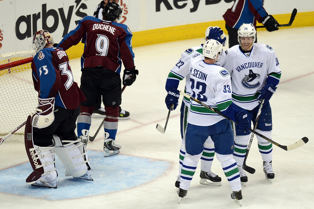 . DENVER, CO. - APRIL 13 : Jannik Hansen of Vancouver Canucks (36) celebrates scoring a goal from goalie Jean-Sebastien Giguere of Colorado Avalanche (35) with the teammates Daniel Sedin (22) and Henrik Sedin (33) during 2nd period of the game at Pepsi Center. Denver, Colorado. April 13, 2013. (Photo By Hyoung Chang/The Denver Post)