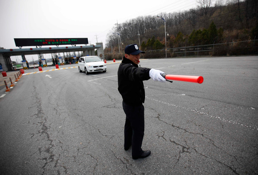 . A South Korean security guard directs traffic as a vehicle transporting employees working at the Kaesong Industrial Complex (KIC) inside the North Korean border, passes through a gate at the South\'s CIQ (Customs, Immigration and Quarantine), just south of the demilitarized zone separating the two Koreas, in Paju, north of Seoul, April 8, 2013. North Korea said on Monday it would withdraw its workers from the Kaesong factory park jointly run with South Korea and temporarily suspend all operations there.   REUTERS/Kim Hong-Ji