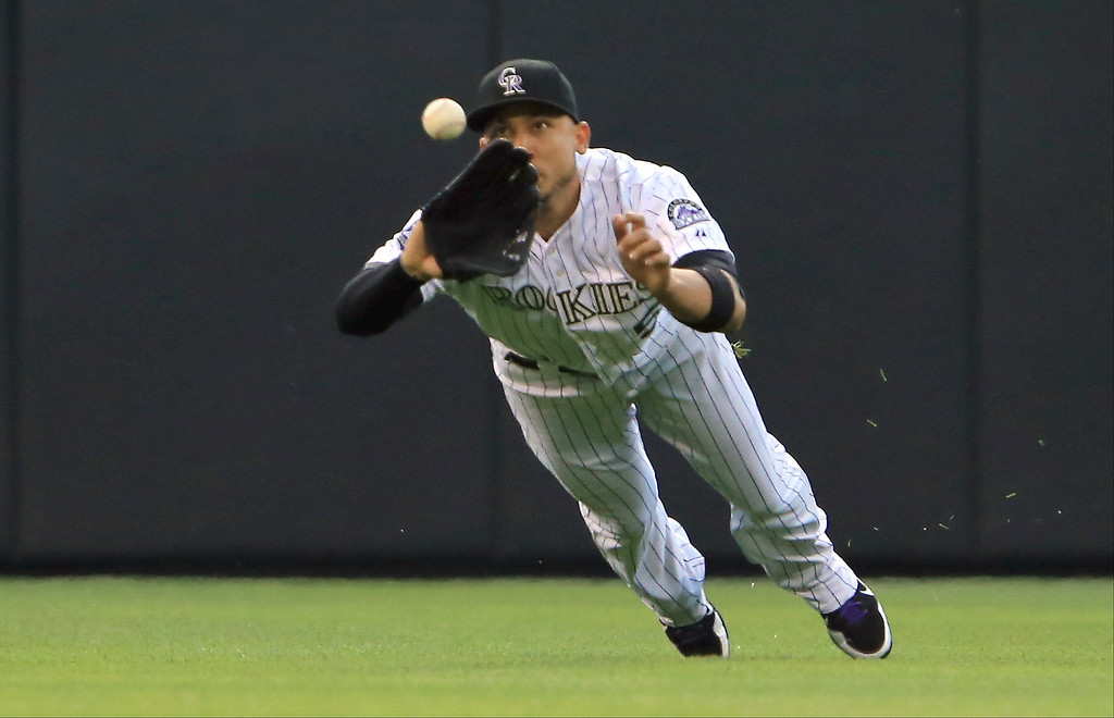 . Left fielder Carlos Gonzalez #5 of the Colorado Rockies dives to catch a line drive by Jeff Kobernus #26 of the Washington Nationals to end the third inning at Coors Field on June 12, 2013 in Denver, Colorado.  (Photo by Doug Pensinger/Getty Images)
