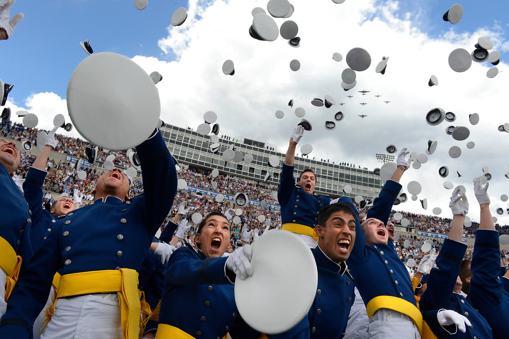 . Graduates toss their caps in the air as World War II aircrafts fly over head during the Untited States Air Force Academy graduation ceremony at Falcon Stadium in Colorado Springs, CO May 29, 2013. Secretary of the Air Force, Mr. Michael B. Donley presented diplomas to the, over 1000,  newly commissioned Second Lieutenants. (Photo By Craig F. Walker/The Denver Post)