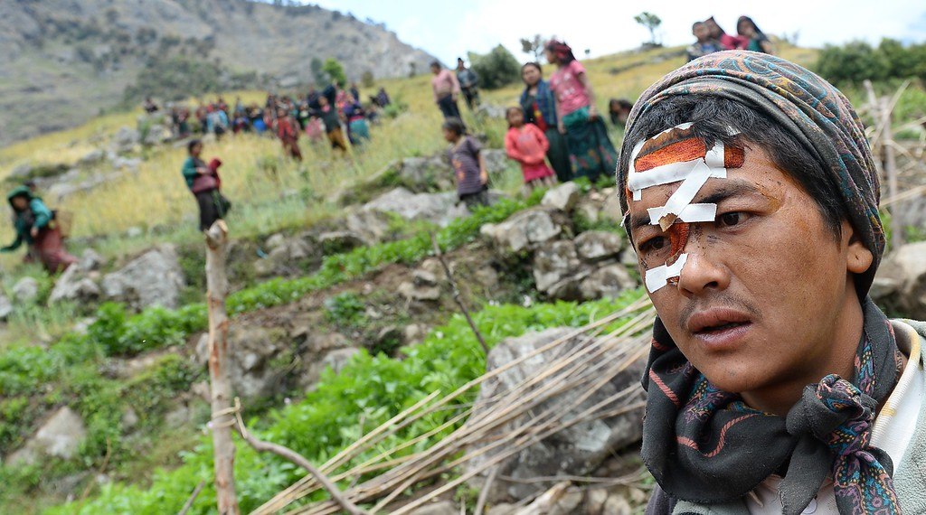 . An injured youth looks down the hill-side towards an Indian Army helicopter at Uiya village, in northern-central Gorkha district on April 29, 2015.   Hungry and desperate villagers rushed towards relief helicopters in remote areas of Nepal, begging to be airlifted to safety, four days after a monster earthquake killed more than 5,000 people.    AFP PHOTO / SAJJAD HUSSAIN/AFP/Getty Images