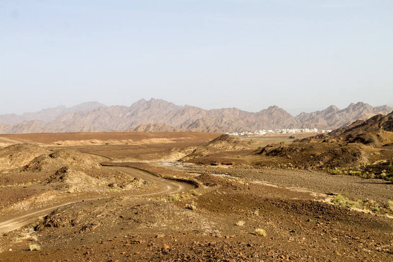Landscape with single track and village in background - Oman
