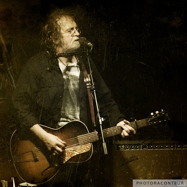 Texas music legend Ray Wylie Hubbard with his fine 1937 Gibson L37 at the Saxon Pub in Austin, Texas on November 3, 2012.  I ordinarily don't add texture to my photos, but Ray Wylie ain't ordinary, y'all.   ©2012 Benjamin Padgett, PhotoRaconteur.com