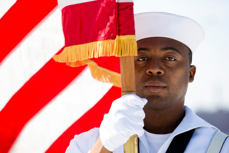 . Seaman Daniel Odoi of the Navy Operational Support Center of New York City presents the American flag during a Memorial Day wreath laying at the Franklin D. Roosevelt Four Freedoms Park on Roosevelt Island, Monday, May 27, 2013, in New York. (AP Photo/John Minchillo)