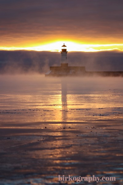 Glowing sunrise behind the Duluth North Pier Lighthouse.  With temperatures well below zero, the lighthouse was surrounded by sea smoke!  Duluth, MN