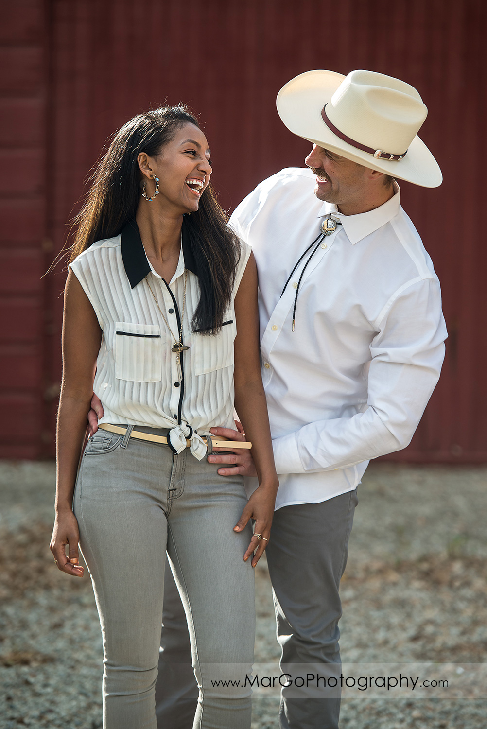 woman in white top and gray jeans and man in white shirt gray jeans and cowboy hat laughing in front of the red wooden barn in Shinn Historical Park and Arboretum in Fremont