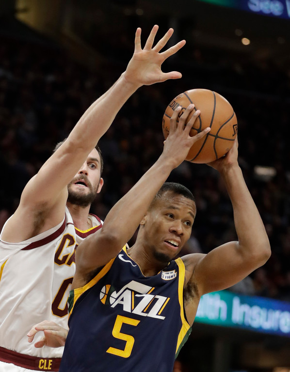 . Utah Jazz\'s Rodney Hood (5) looks to pass against Cleveland Cavaliers\' Kevin Love (0) in the first half of an NBA basketball game, Saturday, Dec. 16, 2017, in Cleveland. (AP Photo/Tony Dejak)