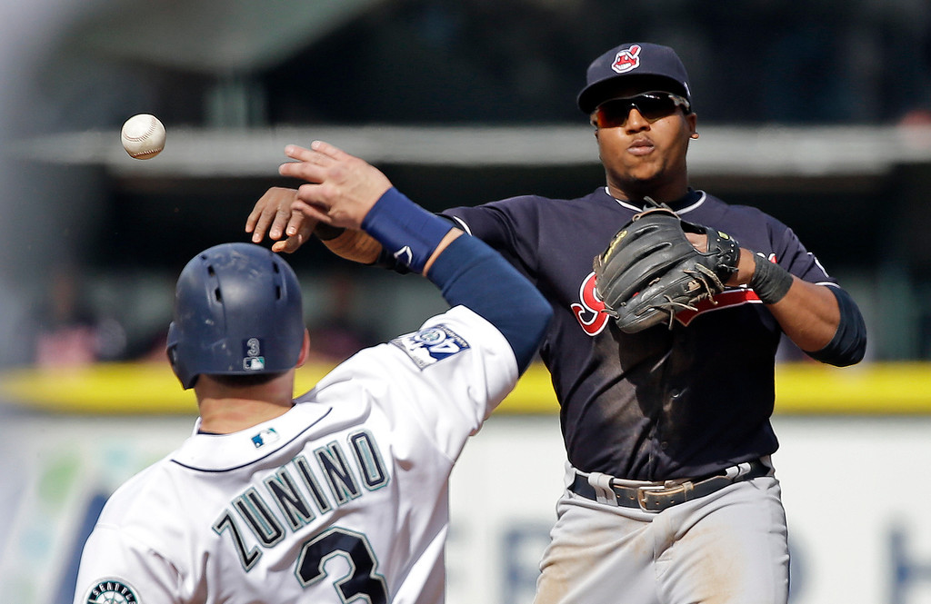 . Cleveland Indians second baseman Jose Ramirez, right, throws to first base after forcing out Seattle Mariners Mike Zunino at second base on a double play in the third inning of a baseball game Saturday, Sept. 23, 2017, in Seattle. (AP Photo/Elaine Thompson)