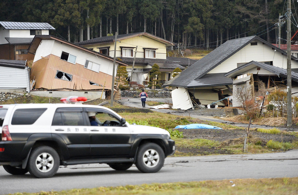 . A Nagano Police vehicle passes by damaged houses Sunday, Nov. 23, 2014 after a strong earthquake hit Hakuba, Nagano prefecture, central Japan, Saturday night. More than 20 people have been hurt after the magnitude-6.8 earthquake shook the mountainous area that hosted the 1998 winter Olympics. (AP Photo/Kyodo News) JAPAN OUT, CREDIT MANDATORY