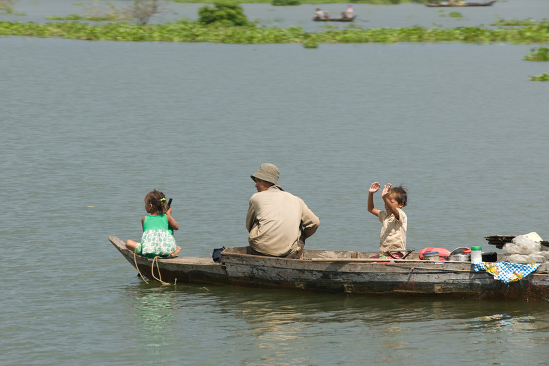 A mom with two kids on a boat on the Tonle Sap river in Cambodia