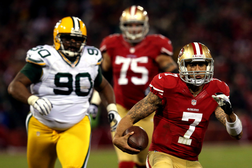 Description of . Quarterback Colin Kaepernick #7 of the San Francisco 49ers runs the ball against nose tackle B.J. Raji #90 of the Green Bay Packers during the NFC Divisional Playoff Game at Candlestick Park on January 12, 2013 in San Francisco, California.  (Photo by Stephen Dunn/Getty Images)