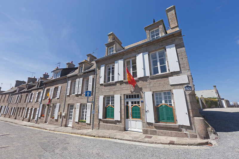 BARFLEUR, FRANCE - JULY 4: Traditional granite houses with Normandy flag in Barfleur, France on July 4, 2011. Barfleur is a picturesque fishing village on the peninsula Cotentin in Basse Normandy.