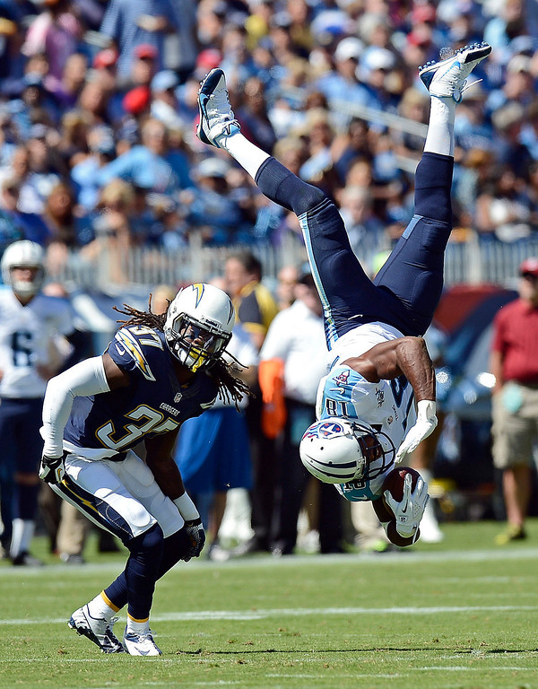 . Tennessee Titans wide receiver Kenny Britt (18) flips upside down after making a catch as he is defended by San Diego Chargers defensive back Jahleel Addae (37) in the second quarter of an NFL football game on Sunday, Sept. 22, 2013, in Nashville, Tenn.  Britt was unable to hold onto the ball and the pass was incomplete. (AP Photo/Mark Zaleski)