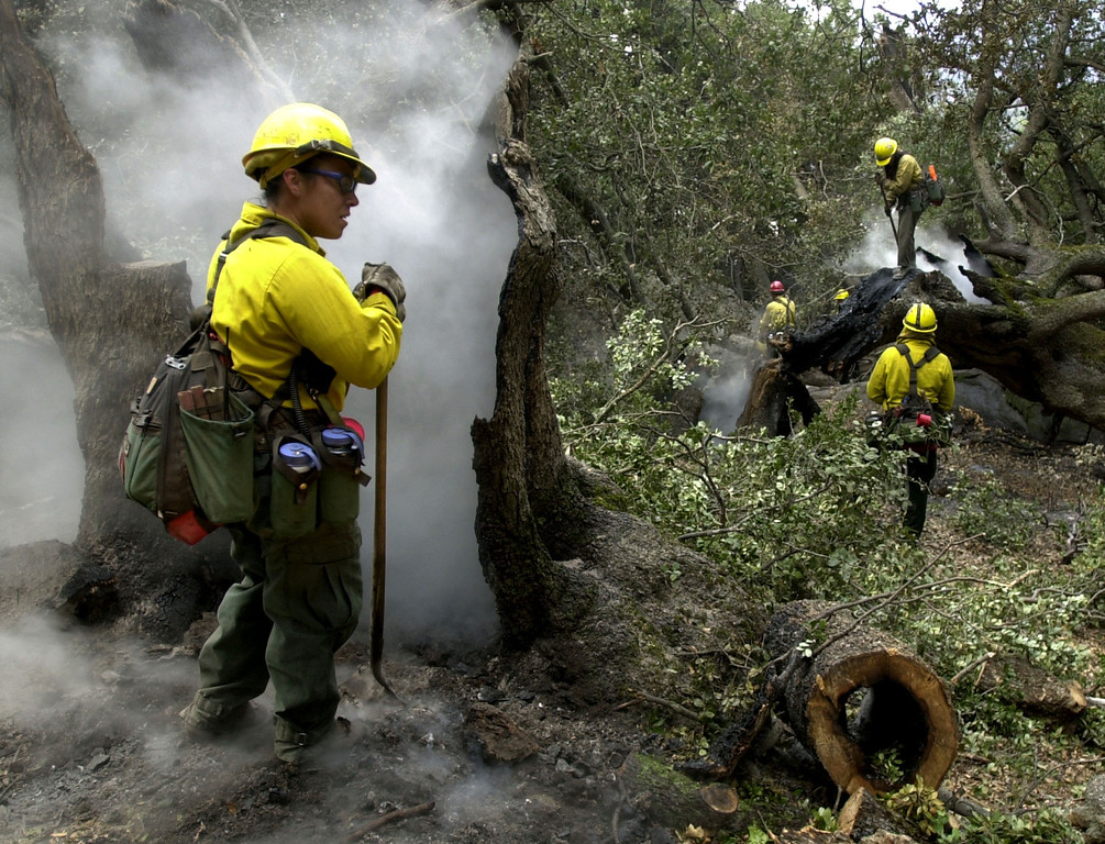 . U.S. Forest Service firefighter Maria Cordoba takes a break from smothering burning embers in Cuyamaca, Calif. Friday, Oct 31, 2003. Cool damp weather is aiding firefighters in controlling the 272,000 acre Cedar fire east of San Diego. (AP Photo/Charlie Riedel)