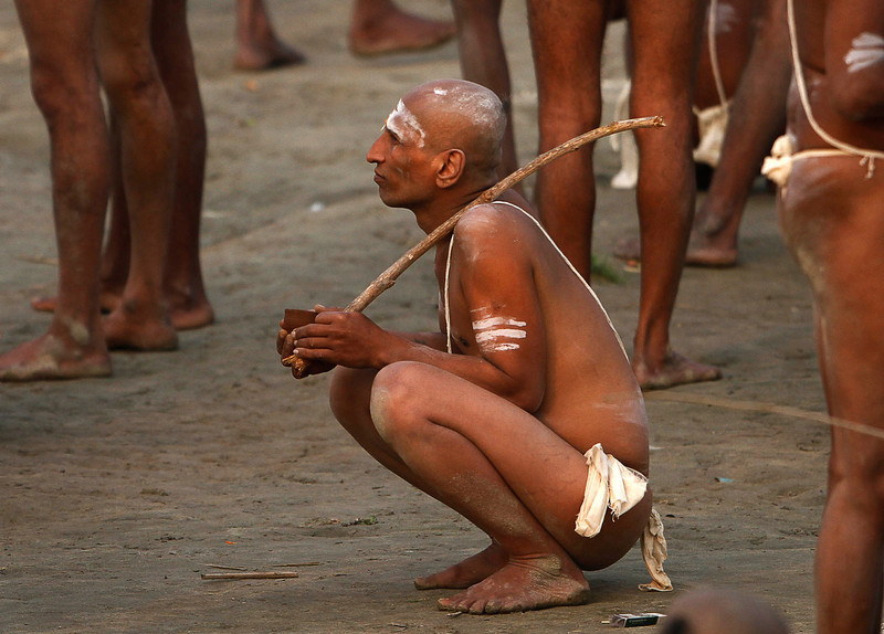 ". A Hindu holy men of the Juna Akhara sect listens to their spiritual leader after rituals that are believed to rid them of all ties in this life and dedicate themselves to serving God as a ""Naga\"" or naked holy men, at Sangam, the confluence of the Ganges and Yamuna River during the Maha Kumbh festival in Allahabad, India, Wednesday, Feb. 6, 2013. The significance of nakedness is that they will not have any worldly ties to material belongings, even something as simple as clothes. This ritual that transforms selected holy men to Naga can only be done at the Kumbh festival.(AP Photo /Manish Swarup)"