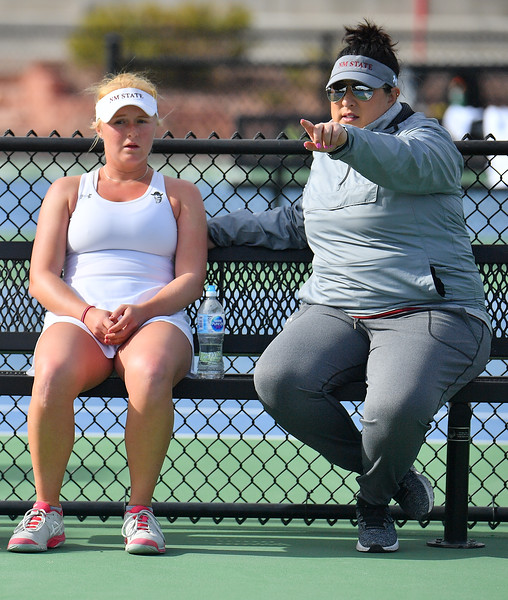 LAS VEGAS, NV - JANUARY 20:  Lindsay Harlas of the New Mexico State Aggies gets instructions from head coach Emily Wang during her match against Tereza Pilzova of the Weber State Wildcats at the Frank and Vicki Fertitta Tennis Complex in Las Vegas, Nevada. Harlas won the match 4-6, 7-5, 1-0 (10-5).