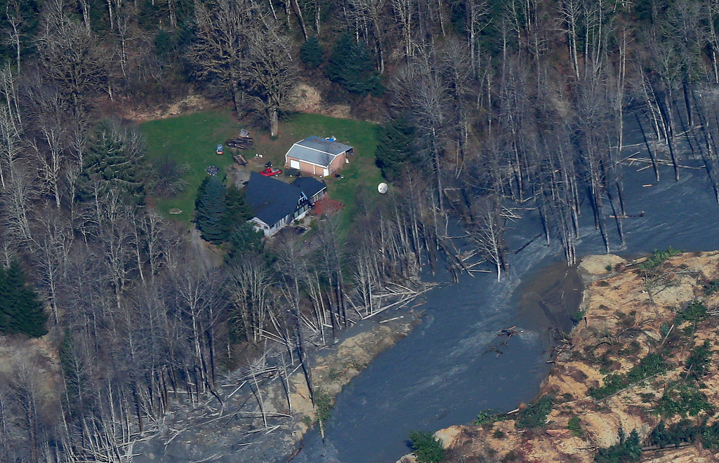 . An intact house sits at left at the edge of the massive mudslide that killed at least eight people and left dozens missing is shown in this aerial photo, Monday, March 24, 2014, near Arlington, Wash. The search for survivors grew Monday, raising fears that the death toll could climb far beyond the eight confirmed fatalities. (AP Photo/Ted S. Warren)