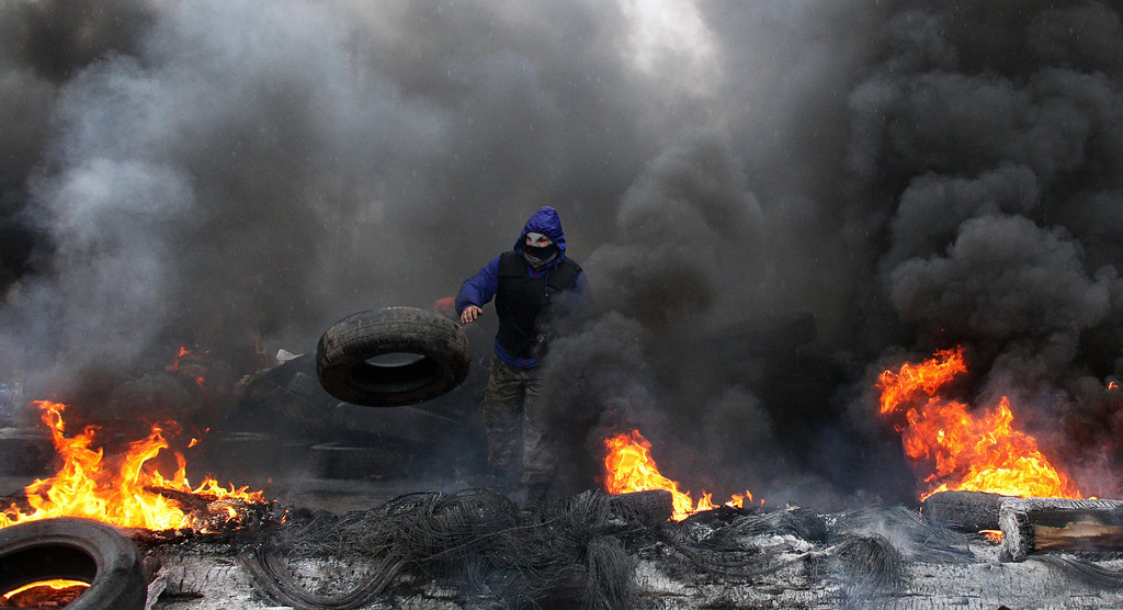 """. A pro-Russian protester burns tires in prepararation for battle with the Berkut (Ukrainian special police forces) on the outskirts of the eastern Ukrainian city of Slavyansk on April 13, 2014. Ukraine on April 13 launched an \""""anti-terrorist operation\"""" in the eastern town of Slavyansk, where pro-Russian gunmen have seized police and security services buildings, Interior Minister Arsen Avakov said. AFP PHOTO / ANATOLIY STEPANOV"""