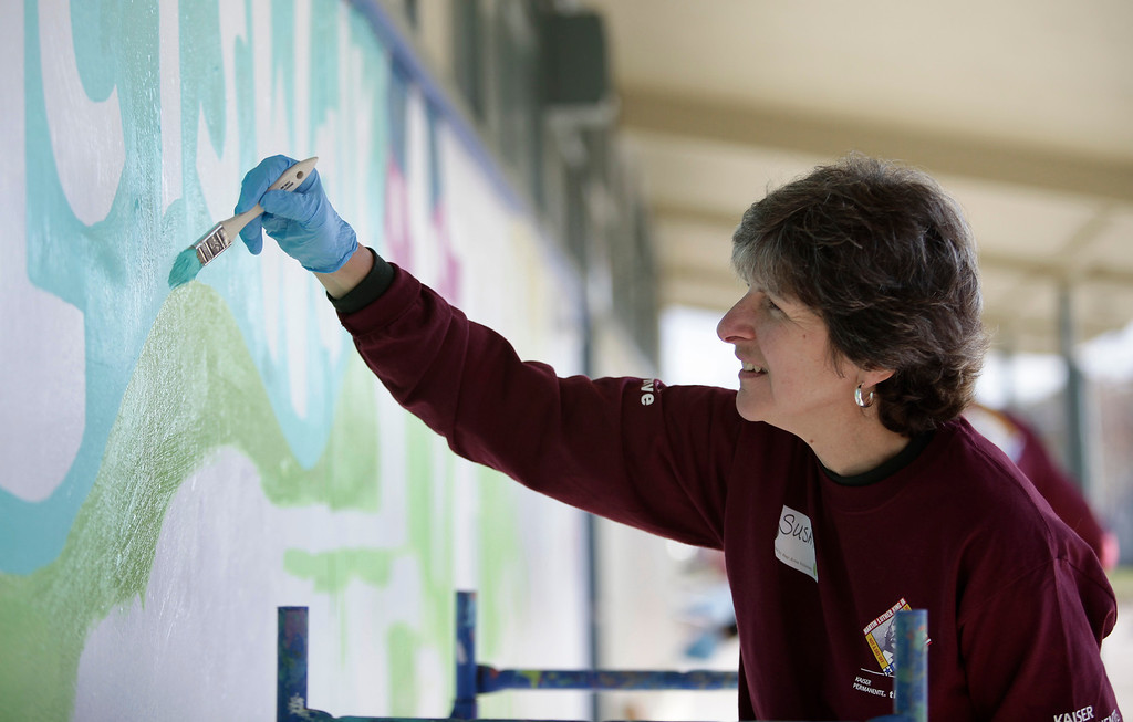 . Kaiser Permanente volunteer, Susan Smarr, M.D., works on a mural at Ryan Elementary School during a Dr. Martin Luther King Jr. day-of-service activity in San Jose, Calif. on Monday, January 21, 2013.  Smarr is the Physician in Chief at Kaiser Permanente in Santa Clara. (Gary Reyes/ Staff)