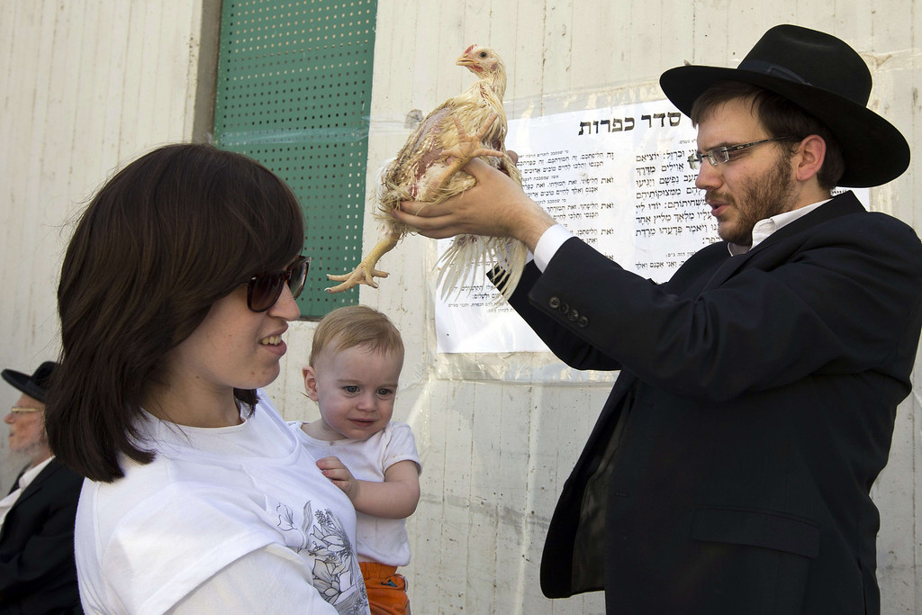 . An Ultra-Orthodox Jewish man swings a chicken over the heads of members of his family during the Kaparot ceremony in the central Israeli city of Bnei Brak near Tel Aviv, on September 11, 2013.  AFP PHOTO/JACK GUEZ/AFP/Getty Images