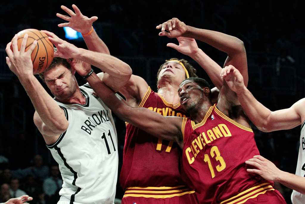 . Brooklyn Nets\' Brook Lopez (11) fights for control of the ball with Cleveland Cavaliers\' Tristan Thompson (13) and Anderson Varejao, center, during the second half of an NBA basketball game, Tuesday, Nov. 13, 2012, in New York. The Nets won 114-101. (AP Photo/Frank Franklin II)