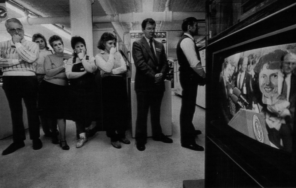 . People watch the memorial ceremony for the crew members killed in the Challenger explosion broadcast from Houston on Jan. 31, 1986. Denver Post Library Archive