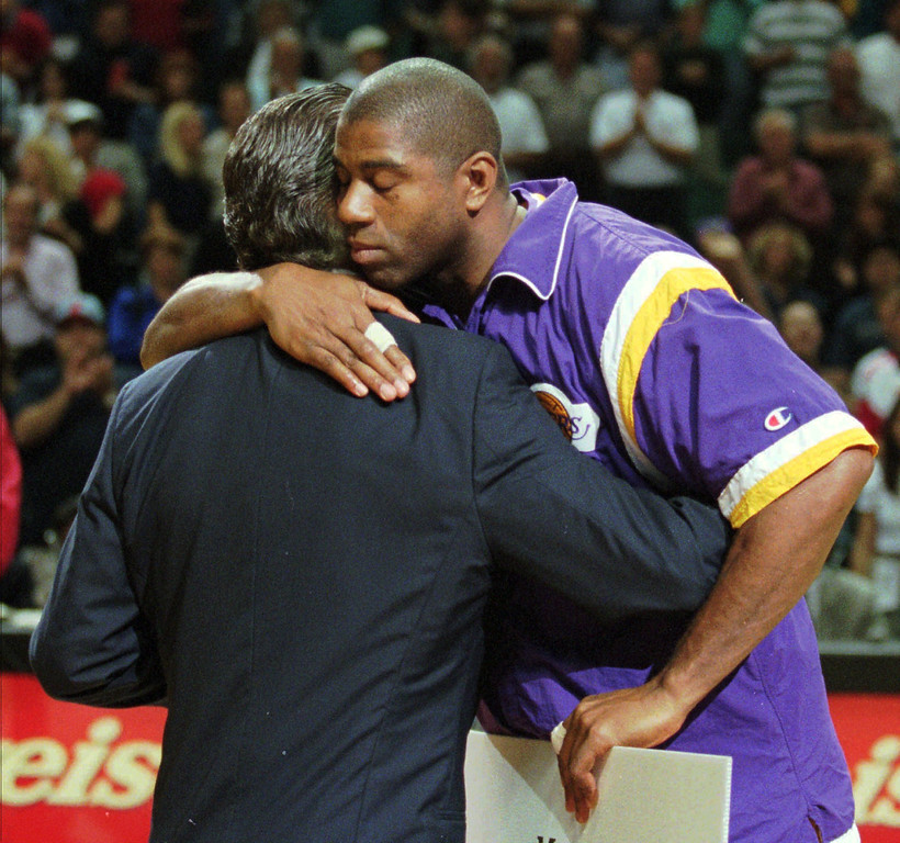 """. Los Angeles Lakers\' Earvin \""""Magic\"""" Johnson hugs Miami Heat\' Head Coach Pat Riley after receiving a $20,000 donation from the Miami Heat to the Magic Johnson Foundation prior to their game in Miami, Fla. Wednesday, March 27, 1996. The Magic Johnson Foundation promotes education and prevention of AIDS among young people. (AP Photo/Jeffrey Boan)"""