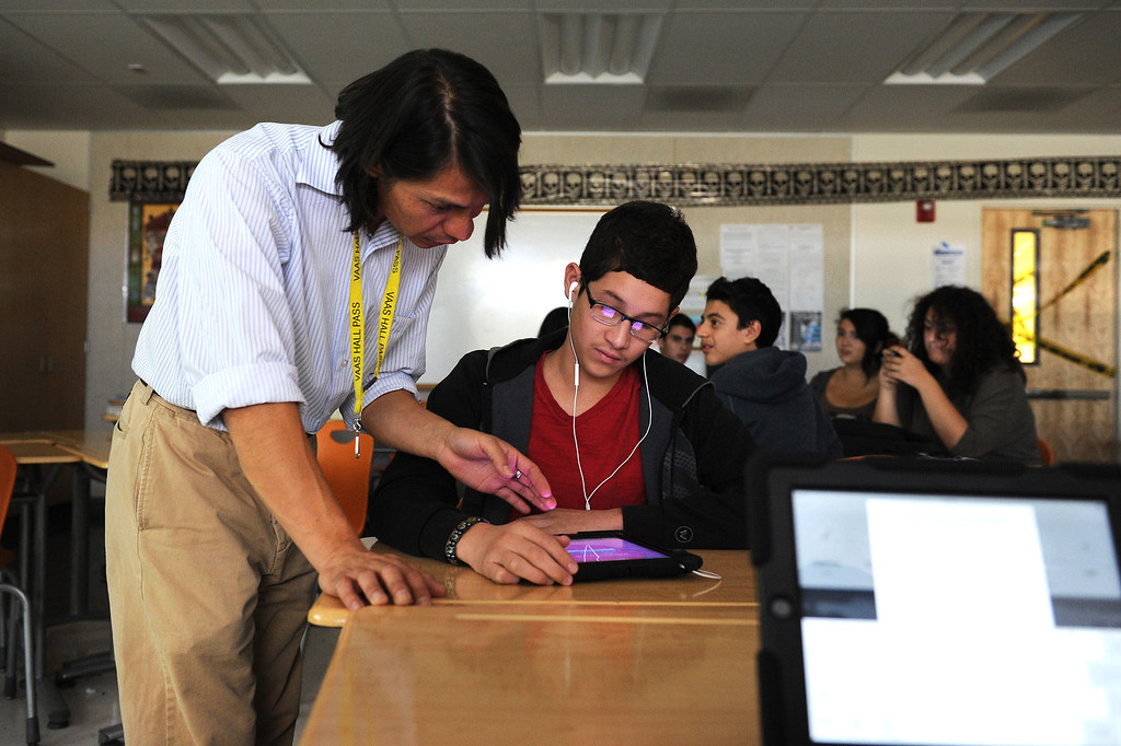 . Valley Academy of Arts & Sciences math teacher Francis Cañas helps a student with his iPad, Tuesday, October 15, 2013. The Valley Academy is one of two LAUSD schools in the San Fernando Valley that are participating in the rollout of the iPad plan. (Photo by Michael Owen Baker/L.A. Daily News)