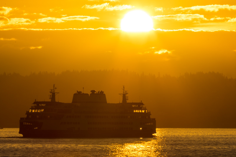 A Washington State Ferry boat is seen in front of the sun rise over the Cascade Mountains of Washington State