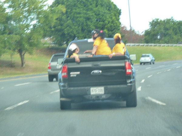 passengers in the bed of a pickup truck