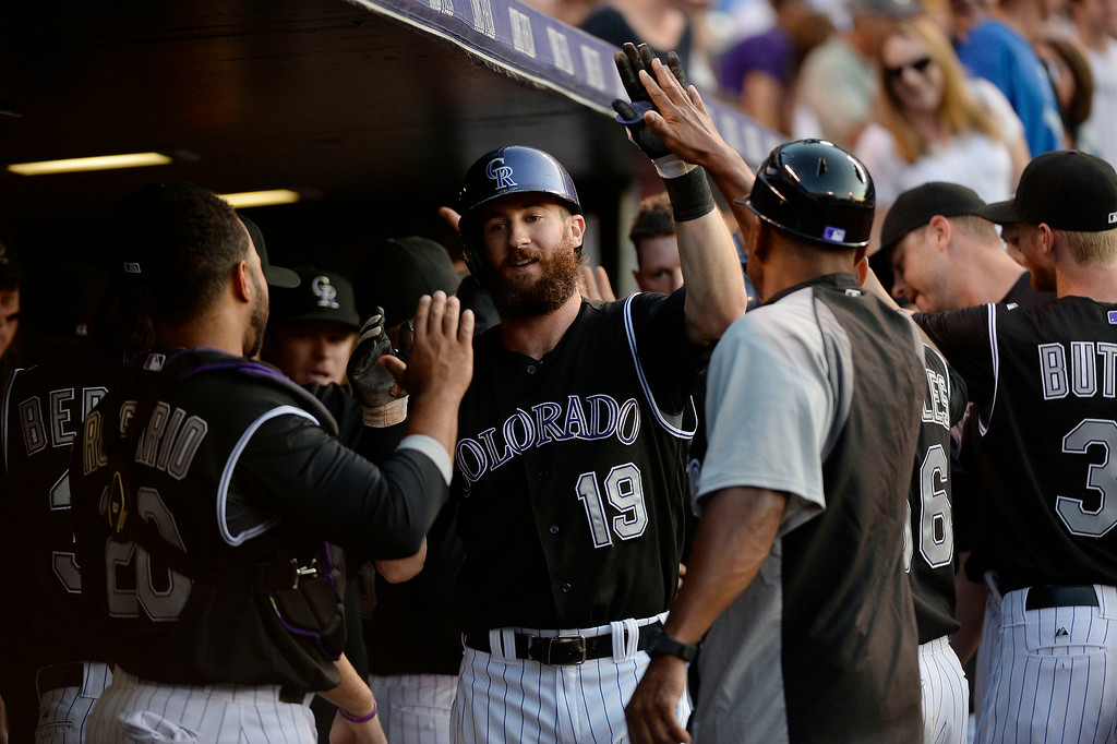 . Colorado Rockies center fielder Charlie Blackmon (19) high fives in the dugout after his line drive homer to right field scoring Colorado Rockies second baseman DJ LeMahieu (9) during the third inning against the  San Diego Padres July 8, 2014 at Coors Field. (Photo by John Leyba/The Denver Post)
