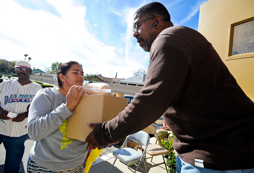 . Volunteer Victor L. Woods gives Amelia Horrera a free Thanksgiving dinner basket given out at 16th Street Seventh-day Adventist Church in San Bernardino on Tuesday, Nov. 26, 2013. The church distributed 175 baskets to families-in-need. (Photo by Rachel Luna / San Bernardino Sun)