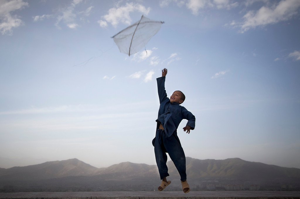 . In this May 13, 2013 file photo made by Associated Press photographer Anja Niedringhaus, an Afghan boy flies his kite on a hill overlooking Kabul, Afghanistan.  (AP Photo/Anja Niedringhaus, File)