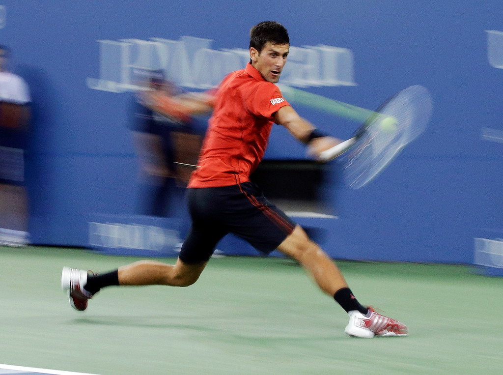 . In this image taken with a slow shutter speed, Novak Djokovic, of Serbia, returns a shot to�Ricardas Berankis, of Lithuania, during the first round of the U.S. Open tennis tournament Tuesday, Aug. 27, 2013, in New York. (AP Photo/Darron Cummings)