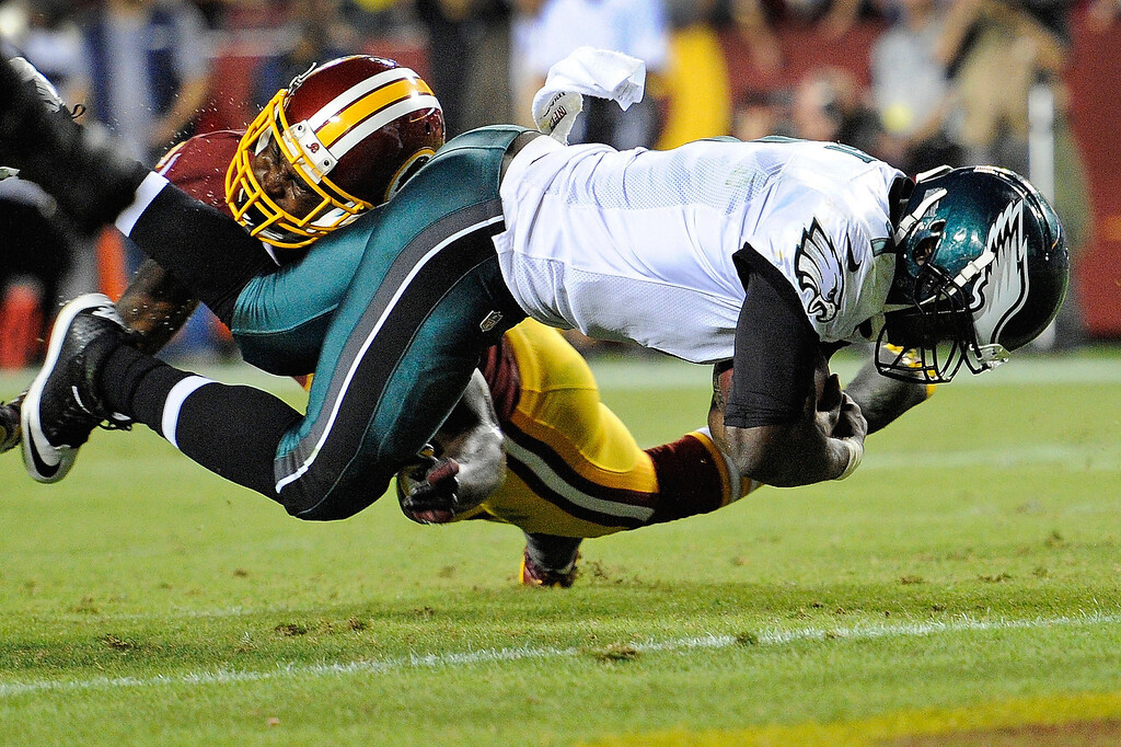 . Philadelphia Eagles quarterback Michael Vick, right, scores a touchdown on the quarterback keeper under pressure from Washington Redskins strong safety Bacarri Rambo during the first half of an NFL football game in Landover, Md., Monday, Sept. 9, 2013. (AP Photo/Nick Wass)