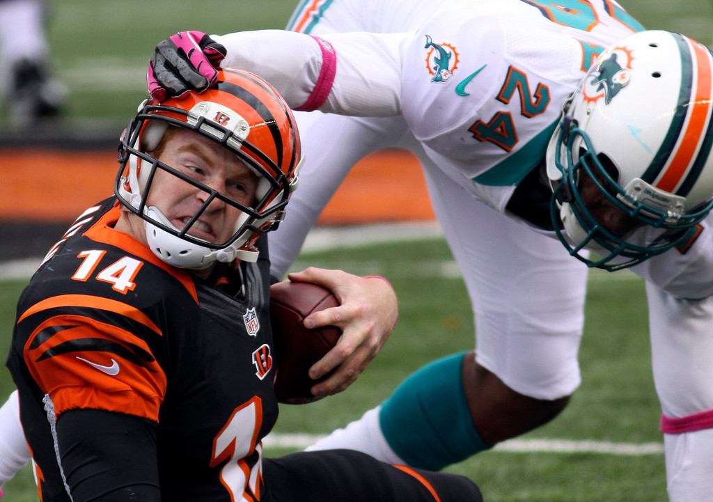 . CINCINNATI BENGALS - Cincinnati Bengals quarterback Andy Dalton (14) is tackled by Miami Dolphins cornerback Sean Smith (24) after a short gain in the second half of an NFL football game on Oct. 7, 2012, in Cincinnati. Miami won 17-13. (AP Photo/Tom Uhlman)