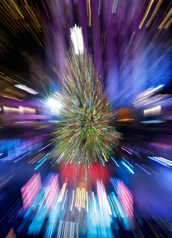 . The Rockefeller Center Christmas tree is lit during a ceremony, Wednesday, Dec. 4, 2013, in New York, in this view in which the lens was zoomed during the exposure. Some 45,000 energy efficient LED lights adorn the 76-foot tree. (AP Photo/Kathy Willens)