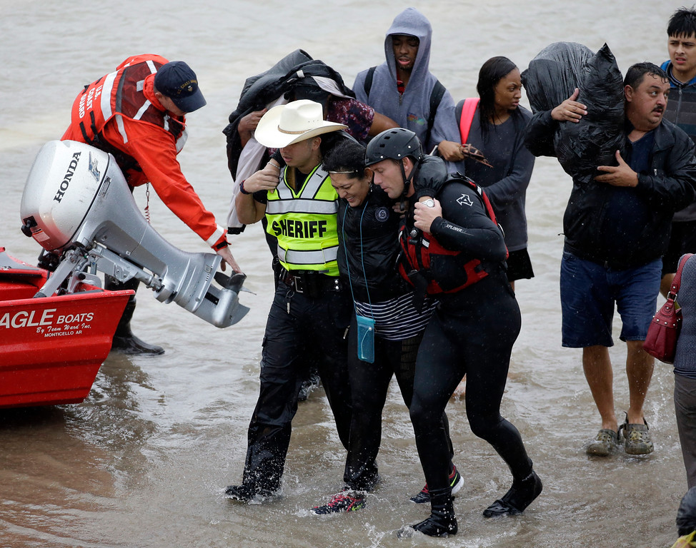 . A woman is helped by rescue personnel while being evacuated as floodwaters from Tropical Storm Harvey rise Monday, Aug. 28, 2017, in Houston. (AP Photo/David J. Phillip)