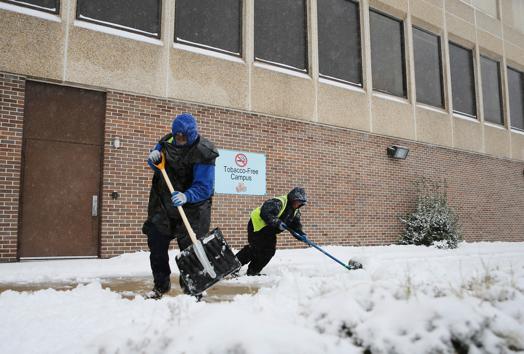 . Robert Galiotis, left, and Hector Sanchez clear the sidewalk at Children\'s Hospital of the King\'s Daughters during a winter storm that brought blizzard conditions to the area, Saturday, Jan. 7, 2016 in Norfolk, Va. (AP Photo/Jason Hirschfeld)