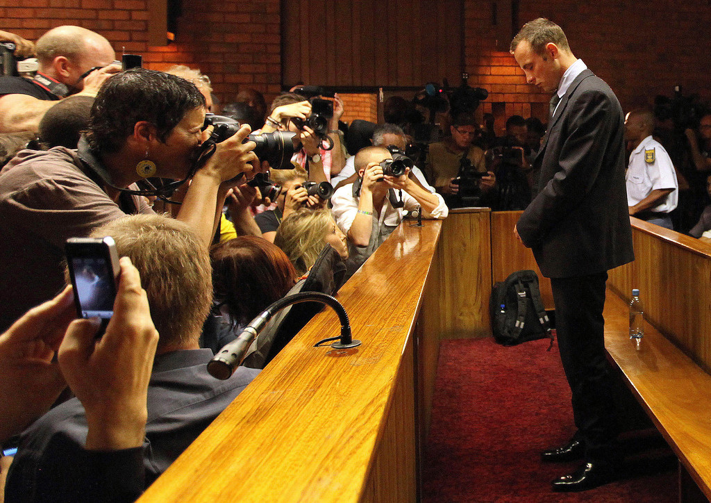 . In this Wednesday, Feb. 20, 2013 file photo Olympic athlete Oscar Pistorius stands inside a court during his bail hearing at the magistrate court in Pretoria, South Africa.  With his athletic triumphs tarnished by the killing of his girlfriend, Reeva Steenkamp. (AP Photo/Themba Hadebe)