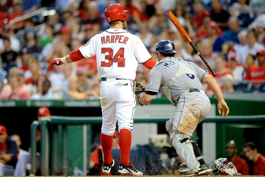 . Michael McKenry #8 of the Colorado Rockies tags Bryce Harper #34 of the Washington Nationals after a strike out in the sixth inning during a baseball on July 2, 2014 at Nationals Park in Washington, DC.  (Photo by Mitchell Layton/Getty Images)