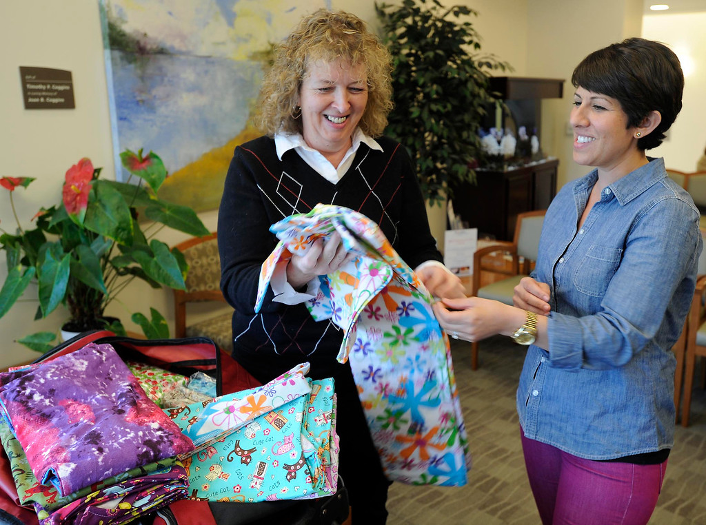 . (l-r) Brenda Jones shows her Hug Wrap to patient Liz Barnett. Jones created her own open-in-the-front wrap when she was undergoing treatment for breast cancer, crafting an option to the hospital gown, utilizing soft and colorful flannel fabrics. Fellow patients loved them and her nonprofit Hug Wraps was born. Jones visited Providence Saint Joseph Medical Center�s Roy and Patricia Disney Family Cancer Center and gave patients free wraps. Burbank, CA 2/22/2013(John McCoy/Staff Photographer)