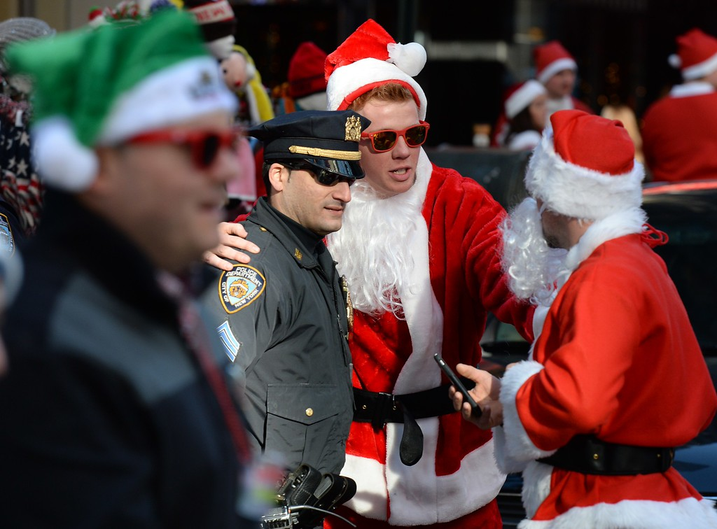 . A Santa poses for a photo with a policeman in Times Square as they gather for the annual Santacon festivities on December 13, 2014 in New York. AFP PHOTO/DON  EMMERT/AFP/Getty Images