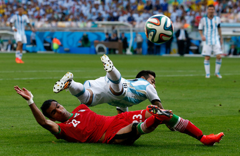 . Iran\'s Mehrdad Pooladi, bottom, challenges Argentina\'s Ezequiel Lavezzi during the group F World Cup soccer match between Argentina and Iran at the Mineirao Stadium in Belo Horizonte, Brazil, Saturday, June 21, 2014. (AP Photo/Jon Super)