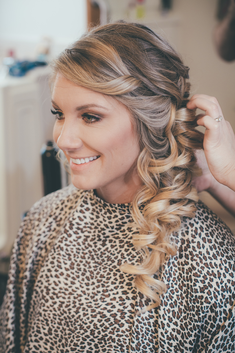 Blonde bride smiling in the mirror as she get her hair done before