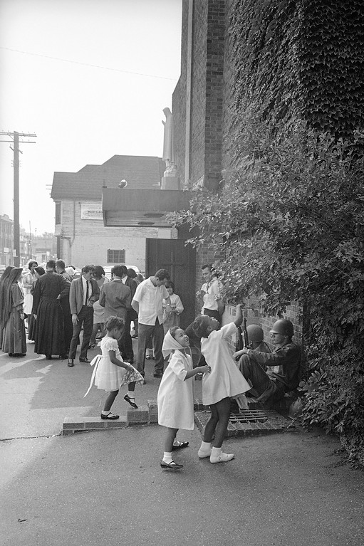 . Children at play outside of Roman Catholic church after having attended services in Cleveland, Ohio, July 24, 1966. Saturday night was quiet after nearly a week of violence and vandalism in this section of Cleveland. (AP Photo)