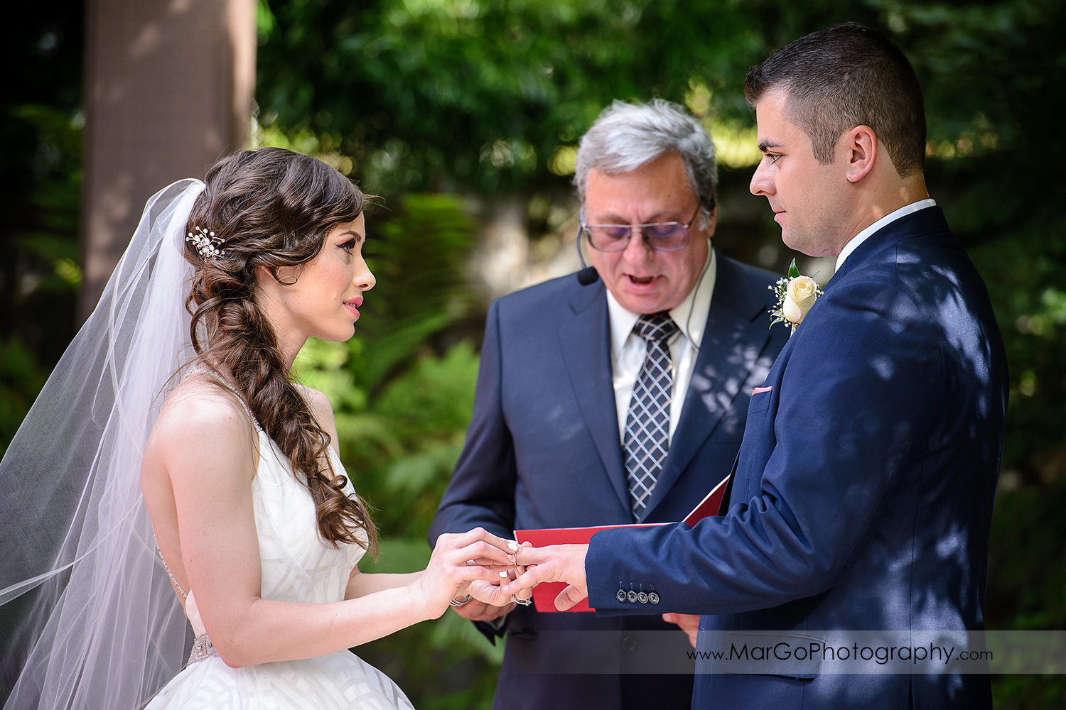 bride putting ring on groom's finger during wedding ceremony at Saratoga Foothill Club
