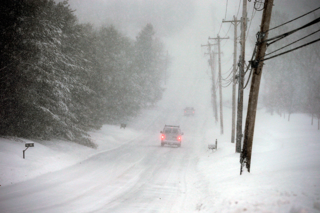 . Cars creep along on a snow-covered rural road near Newtown, Pa., Thursday, Feb. 13, 2014. After pummeling wide swaths of the Southeast, a winter storm dumped more than a foot of snow in parts of the Mid-Atlantic region as it marched Northeast and threatened more power outages, traffic headaches and widespread closures for millions of residents.  (AP Photo/Mel Evans)